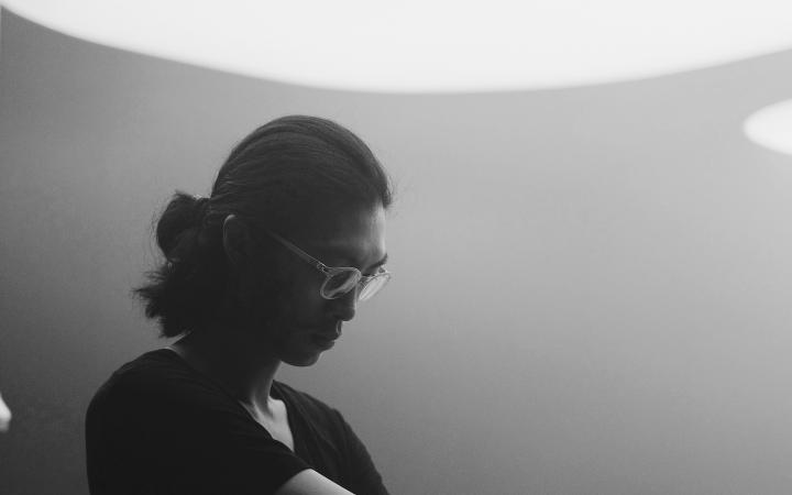Zu sehen ist ein Mann, welcher im stehen an einem Mixpult steht. Er hat eine Brille und lange Haare, welche er zu einem Zopf zusammen gebunden hat.