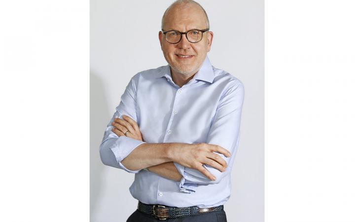 Harald H.H.W. Schmidt hält lächelnd ein Poster mit einer Abbildung des »Flavor Network« des BarabásiLab