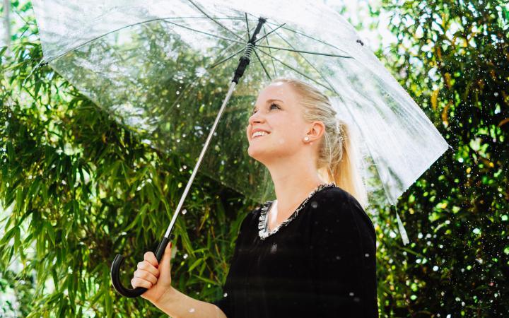 Woman standing with umbrella under the raindance installation