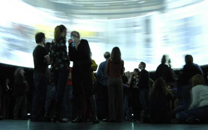Persons standing in the middle of a huge 360° screen