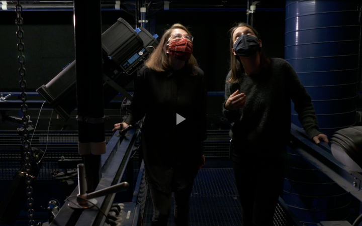 Two women stand in a passageway with technical equipment behind the scenes at the ZKM and look around.