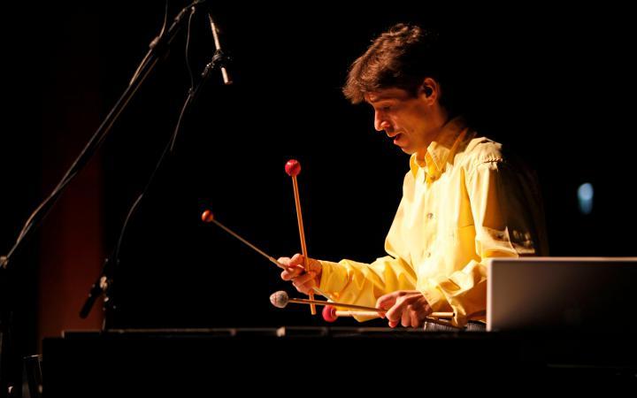 Ein Mann spielt mit gesenktem Bilck auf einem großen Xylophon mit vier Klöppeln von denen er jweils zwei überkreuzt in der Hand hält.