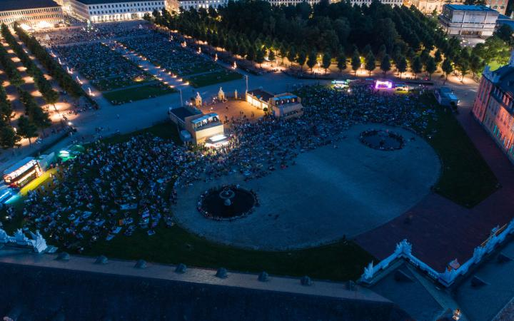 The photo shows an overview of the visitors to the premiere of the Schlosslichtspiele 2019. The photo was taken with a drone above the castle and shows a large crowd of people on the green meadow in front of Karlsruhe Castle.