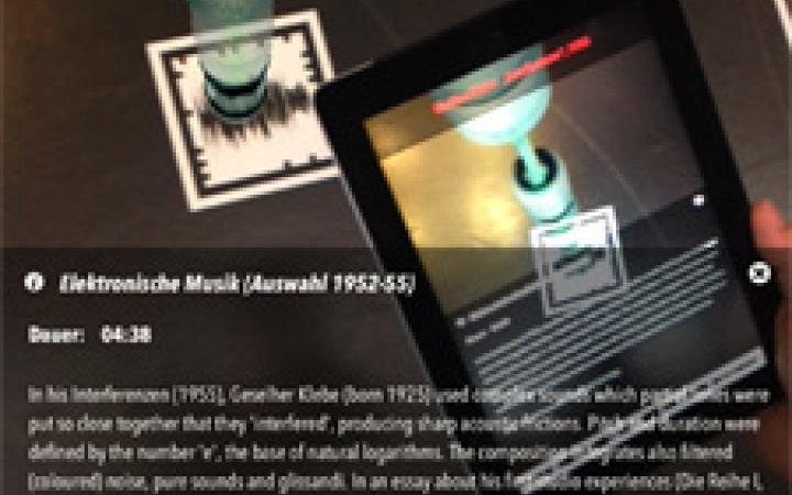 Ausstellungsansicht des Klangpfades. Ein Besucher liest auf einem Tablet Informationen zu Giselher Klebes Stück Interferenzen von 1955.