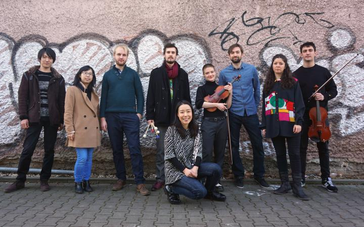Das Bild zeigt die StipendiatInnen der Internationalen Ensemble Modern Akademie (IEMA) vor einer vollgesprühten Backsteinwand
