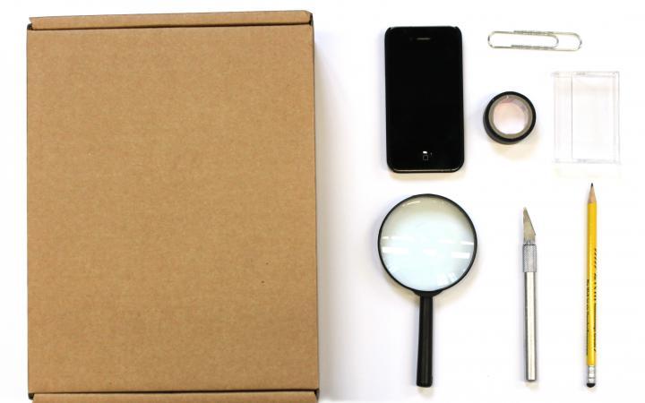 Zu sehen ist eine Lupe, ein Smartphone, eine Pappkiste, ein Cutter, ein Stift, eine Büroklammer, eine Kassettenhülle und Klebeband.