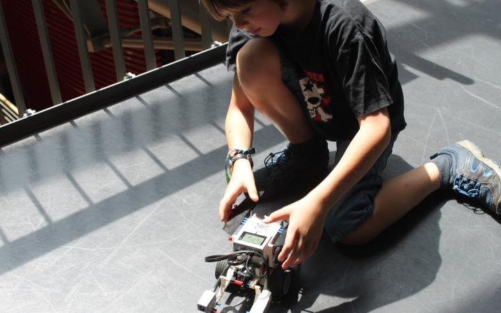 A boy is kneeling on the floor next to a lego-robot.