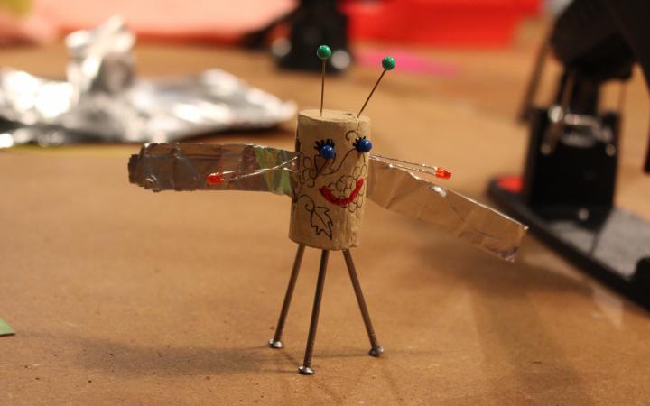 Ein Korken, der zu einer kleinen Figur umgewandelt und mit Flügeln ausgestattet wurde, steht auf einem Tisch mit allerlei Bastelutensilien.
