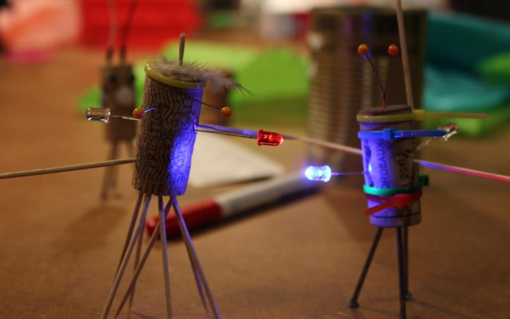 Zwei Korken, die zu kleinen Figuren umgewandelt wurden und mit LEDs ausgestattet sind stehen auf einem Tisch mit allerlei Bastelutensilien.