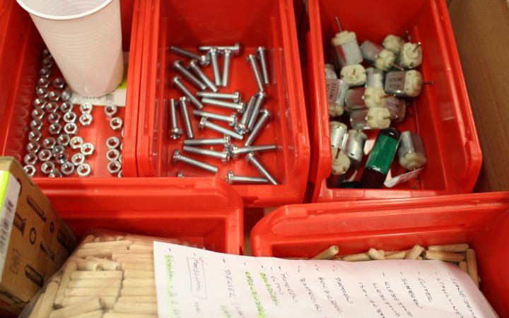 Mehrere Rote Schuber für Handwerkszubehör in denen diverse Schrauben, kleine Motoren oder Nägel liegen.
