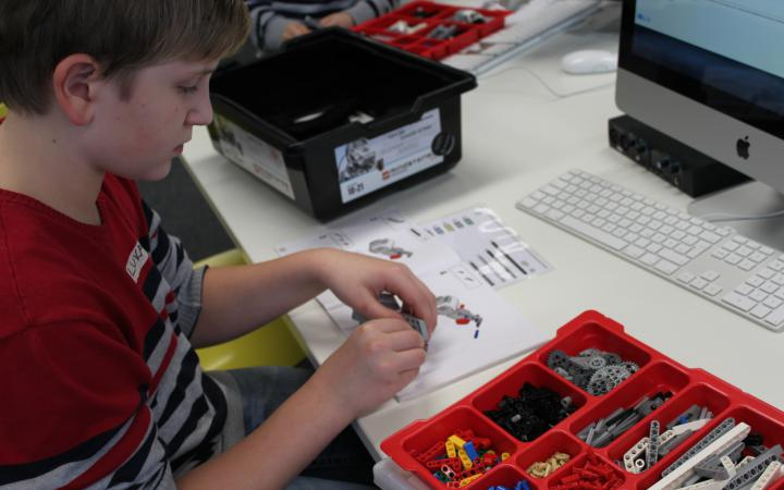 A boy is constructing a lego-robot. On the table he is sitting at are boxes filled with robot parts.
