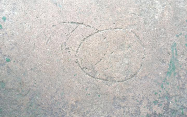 Circular shapes carved on a stone surface.