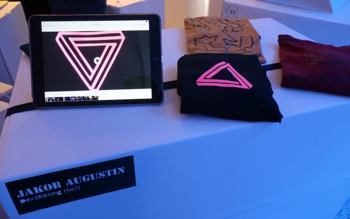 Zu sehen ist ein Ipad und T-Shirts auf einem Tisch im Rahmen einer Veranstaltung der Kulturakademie.
