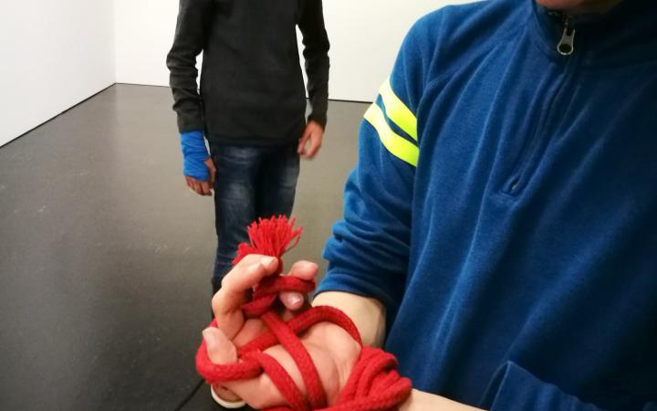Zu sehen sind die Hände eines Schülers mit einem roten Seil geknebelt im Rahmen der Veranstaltung »Art im Puls«.