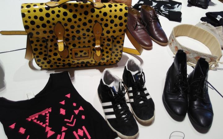 Zu sehen ist eine gelbe, gepunktete Tasche umgeben von Schuhen und einem T-Shirt.