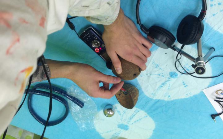 Ein Mann nimmt mir dem Fieldrecorder die Geräusche von verschiedenen Gegenständen auf, die vor ihm auf dem Tisch liegen.