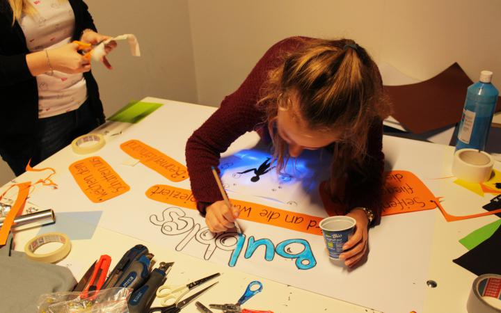 A pupil is creating an interactive poster