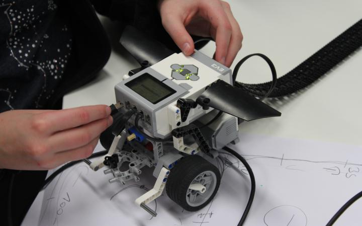 A child is constructing a lego-robot, in this moment it attaches a cable on the front.