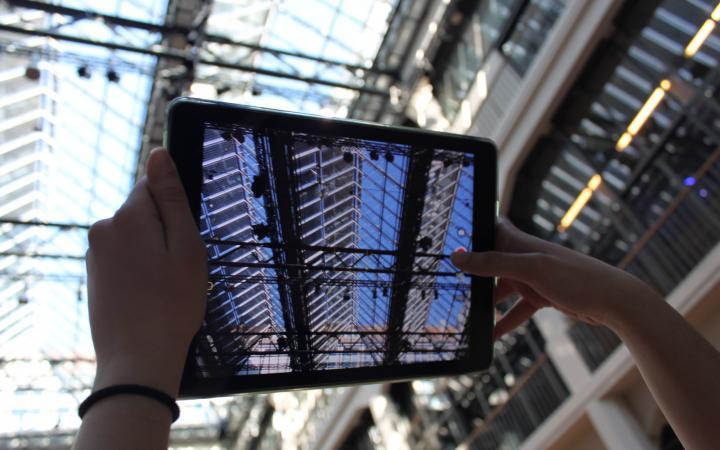 Zwei Hände die mit einem iPad ein Foto von der Decke des ZKM aufnehmen im Rahmen der Veranstaltung »Global Sound«.