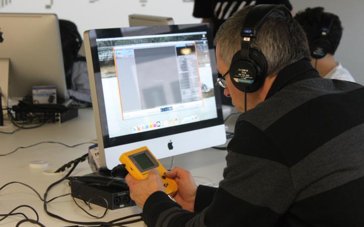 Ein Mann hält einen gelben Gameboy vor sich, mit dem er Sounds kreieren kann.