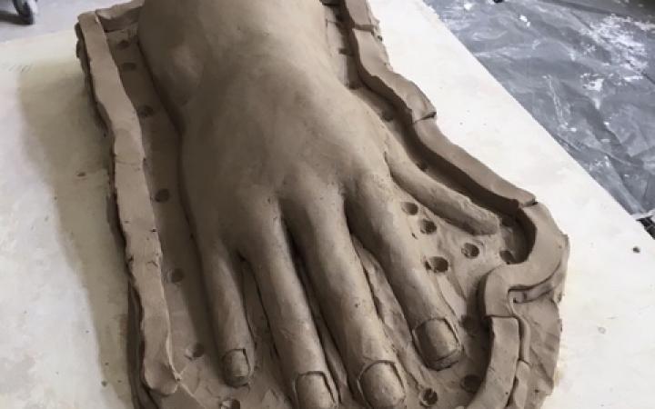 Zu sehen ist eine überdimensionale Hand aus Ton