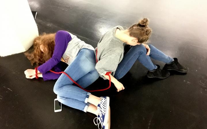 Zwei Schülerinnen liegen mit einem roten Seil am Boden im Rahmen der Veranstaltung »Art im Puls«.