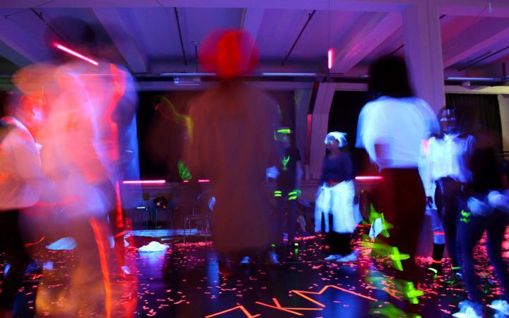 Zu sehen sind viele Menschen in einem dunklen Raum mit leuchtendenden Schriftzügen im Rahmen einer Veranstaltung der Kulturakademie.