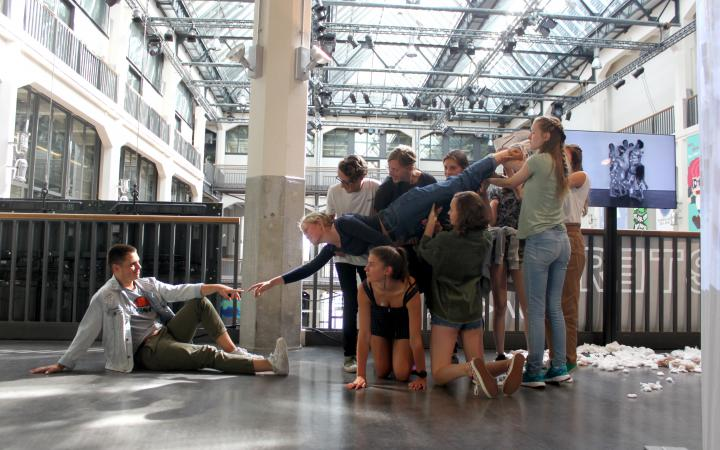 Rechts hält eine Gruppe von Schülern eine Schülerin, die ihre Hand zu einem sitzenden Schüler links streckt im Rahmen einer Veranstaltung der Kulturakademie.