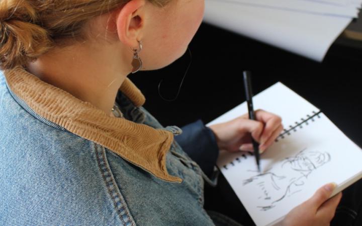 Foto einer jungen Frau beim Zeichnen
