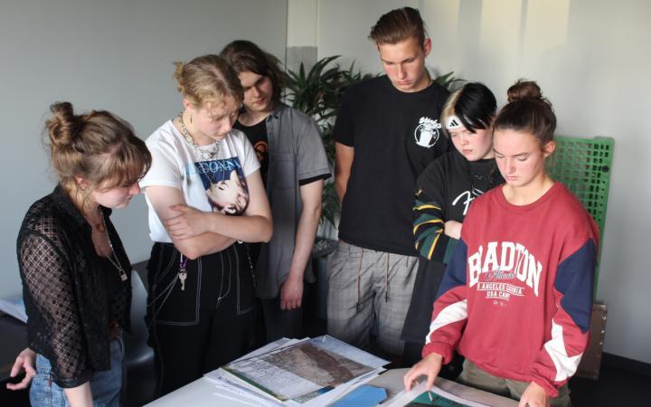 Ein Foto von sechs SchülerInnen vor einem Tisch mit Projektskizzen.