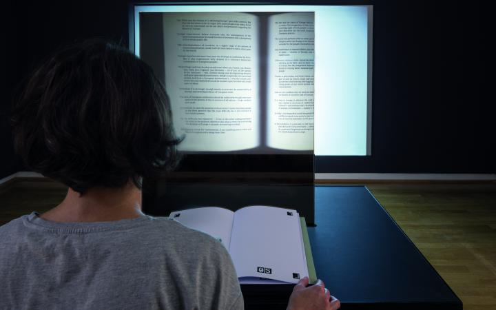 You can see the back of a person's head, and in front of it is an open book. On the wall opposite is a projection of an opened book.