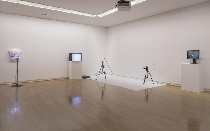 You can see the corner of a room with four objects. You can see two screens and two tripods, which are placed in a large distance to each other.