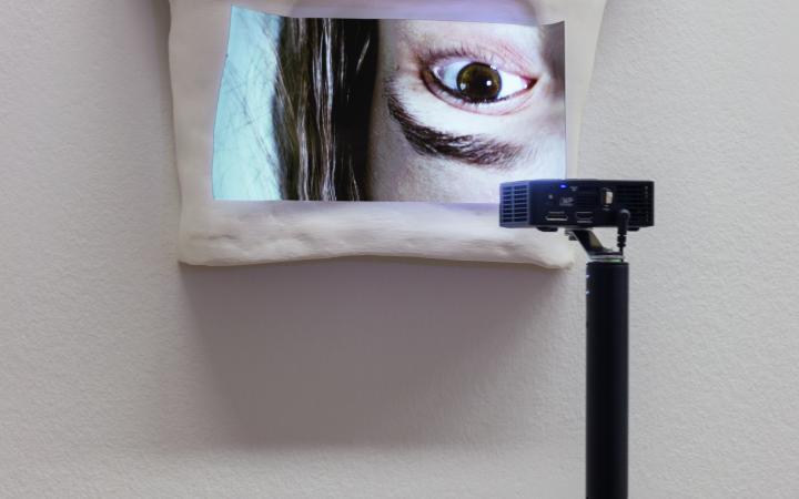 Zu sehen ist ein weißes Objekt, welches an der Wand hängt. Auf dem Objekt ist das Bild eines Abschnitts aus dem Gesicht einer Frau.