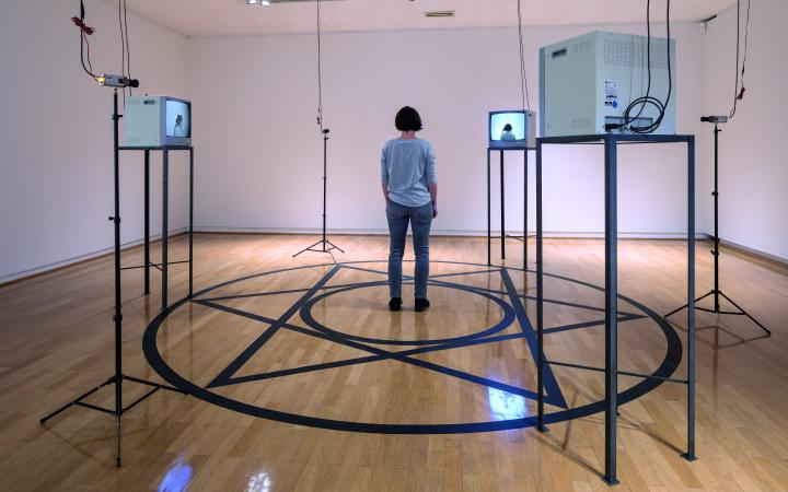 A room can be seen in which four monitors stand on a rack. A circle is glued to the floor, in the middle of which is a star and another circle. In the middle is a woman with her back to the viewer.