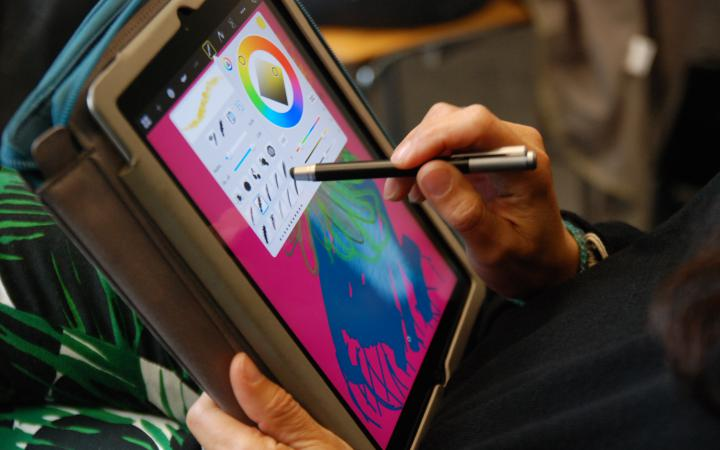 Someone is painting with a stylus, a special pen for displays, on an iPad.