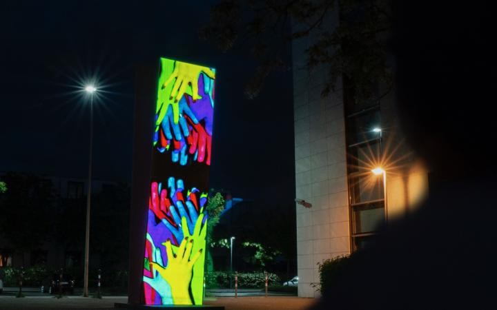Many hands are projected on a column. One set of hands stretches from bottom to top towards the other set of hands and vice versa. It is night.