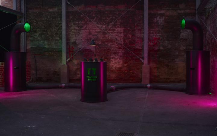 Ein rot erleuchteter Raum mit der Talking-Tubes-Installation: ein Steuerungspult zwischen zwei großen Röhren