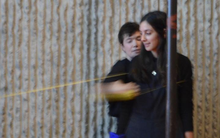 Das Foto zeigt zwei Frauen, die schräg hinterinander stehen. Sie tragen dunkle Kleidung und stehen vor einer grauen Wand. Verschiedene Seile sind schemenhaft zu erkennen.
