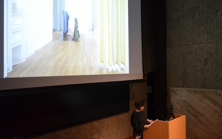 Auf dem Foto ist ein Ausschnitt eines großen brutalistischen Vortragsaales zu sehen. Eine Frau steht am Holzpult während hinter ihr eine gigantische Leinwand ein Foto zeigt, wo verschiedene Stoffe hängend zu sehen sind.