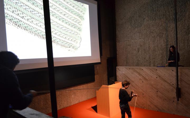 Das Foto zeigt den Beginn der Lecture-Performance. Zwei Frauen stehen sich auf einer Holzempore gegenüber, während eine Performerin zwischen ihnen ein Seil von der einen Person zu anderen spannt. Der Boden in der Mitte ist mit einem roten Teppich ausgeleg