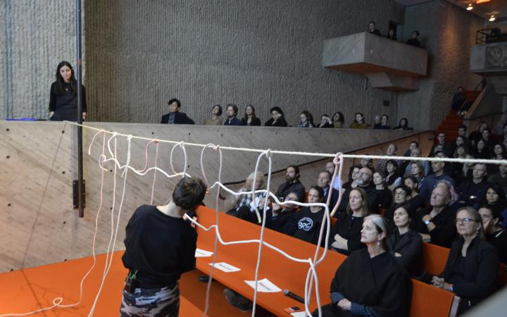 Photo of a full lecture hall. The artist Judith Raum creates a net in the foreground.