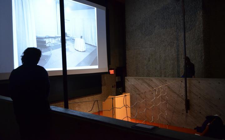 Auf dem Foto ist der brutalistische Vortragssaal abgedunkelt während auf der großen Leinwand ein Büroähnlicher Raum mit Vorhängen zu sehen ist. In der Mitte hängt das Netz aus Seilen, was einem Volleyballnetz ähnelt.
