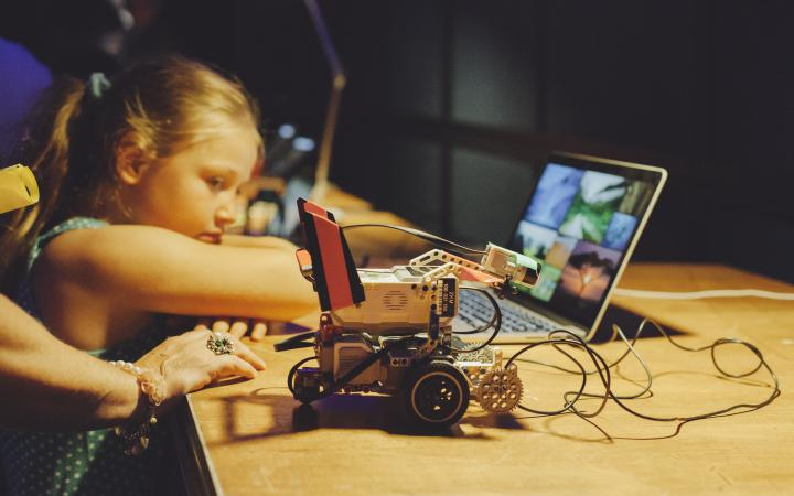 A child is leaning against a table with a small robot standing on it