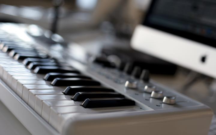 Ein Keyboard in Nahaufnahme, angeschlossen an einem Computer im Hintergrund.