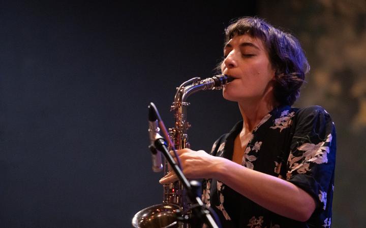 Ein Foto der Musikerin Lea Bertucci, die grade Saxofon spielt.
