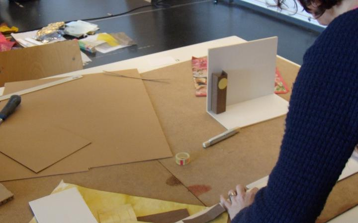 Eine Frau arbeitet an einer Miniaturkulisse.