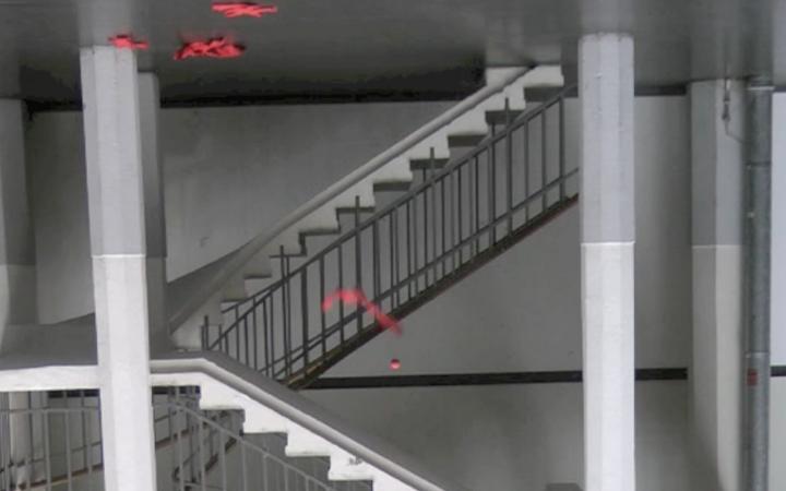 Ein Treppenhaus ist verkehrt herum zu sehen, ein roter Stoffstreifen und ein Ball scheinen nach oben zu fallen.