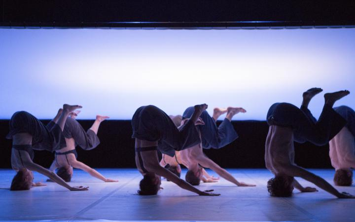 Seven different dancers have bent their legs in the headstand. In the background there is a large, milky screen.