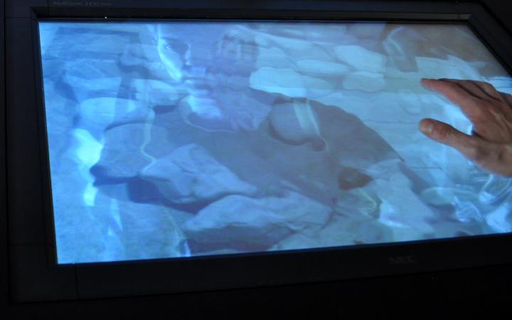 Das Bild zeigt einen Mann, der auf einen Monitor sieht, der einer Wasseroberfläche gleicht.