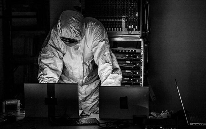 Ein Mensch in einem weissen Schutzanzug hinter einem Pult mit Laptops